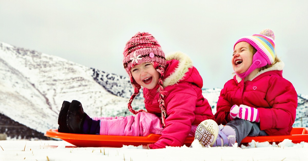 Two laughing kids sledding with a mountain scene in background