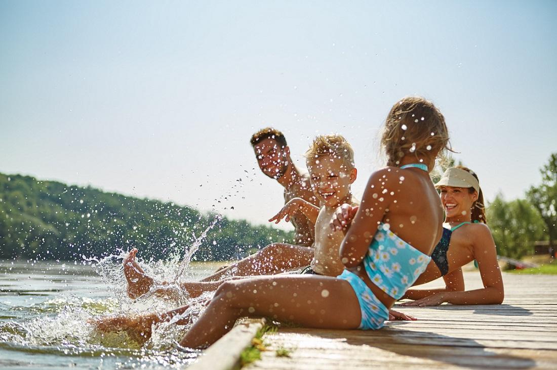 Glückliche Familie am See im Sommer hält die Füße ins Wasser