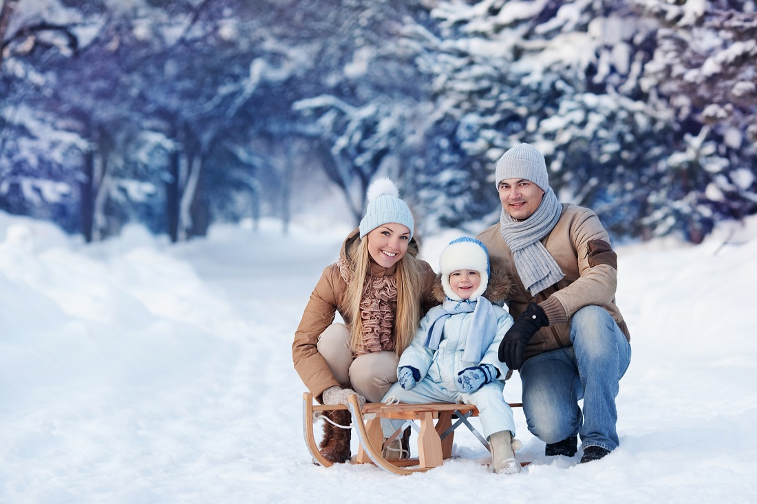 Portrait of Young family and his baby in a winter park