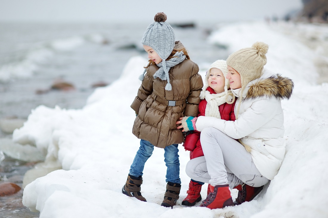 Young mother and her two daughters by the sea on winter