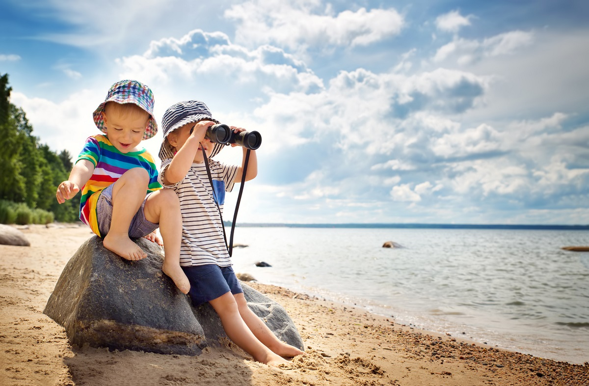 Babygirl and babyboy sitting on the beach in summer hats