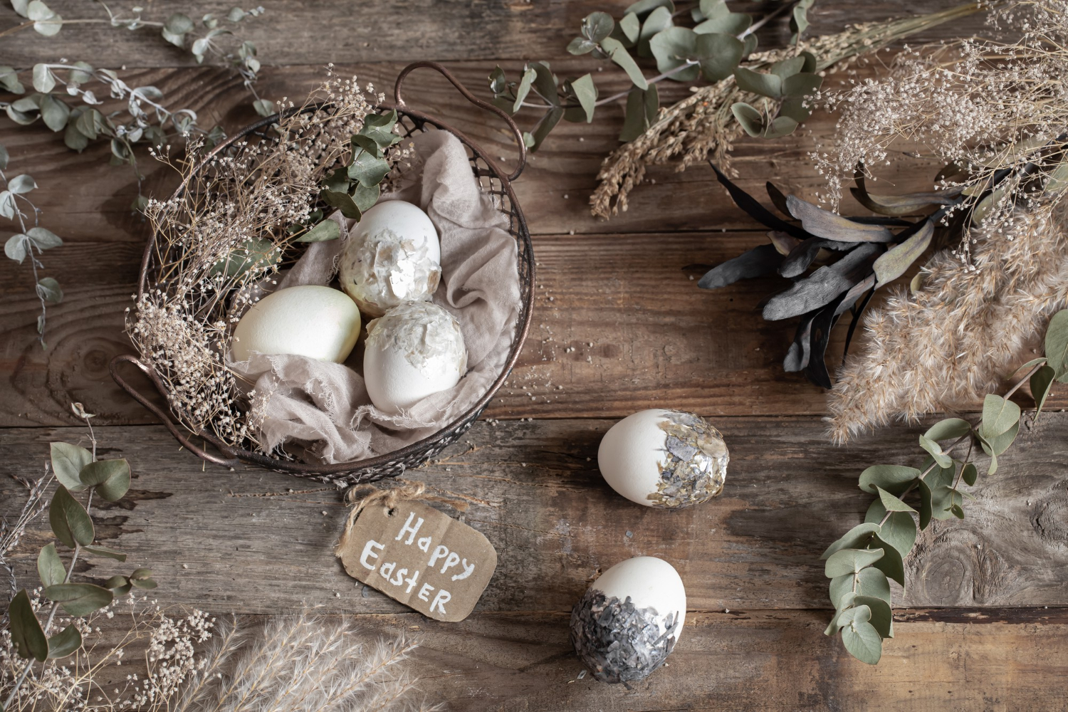 easter-eggs-in-a-decorative-basket-with-dried-flowers-on-a-wooden-table-happy-easter-concept